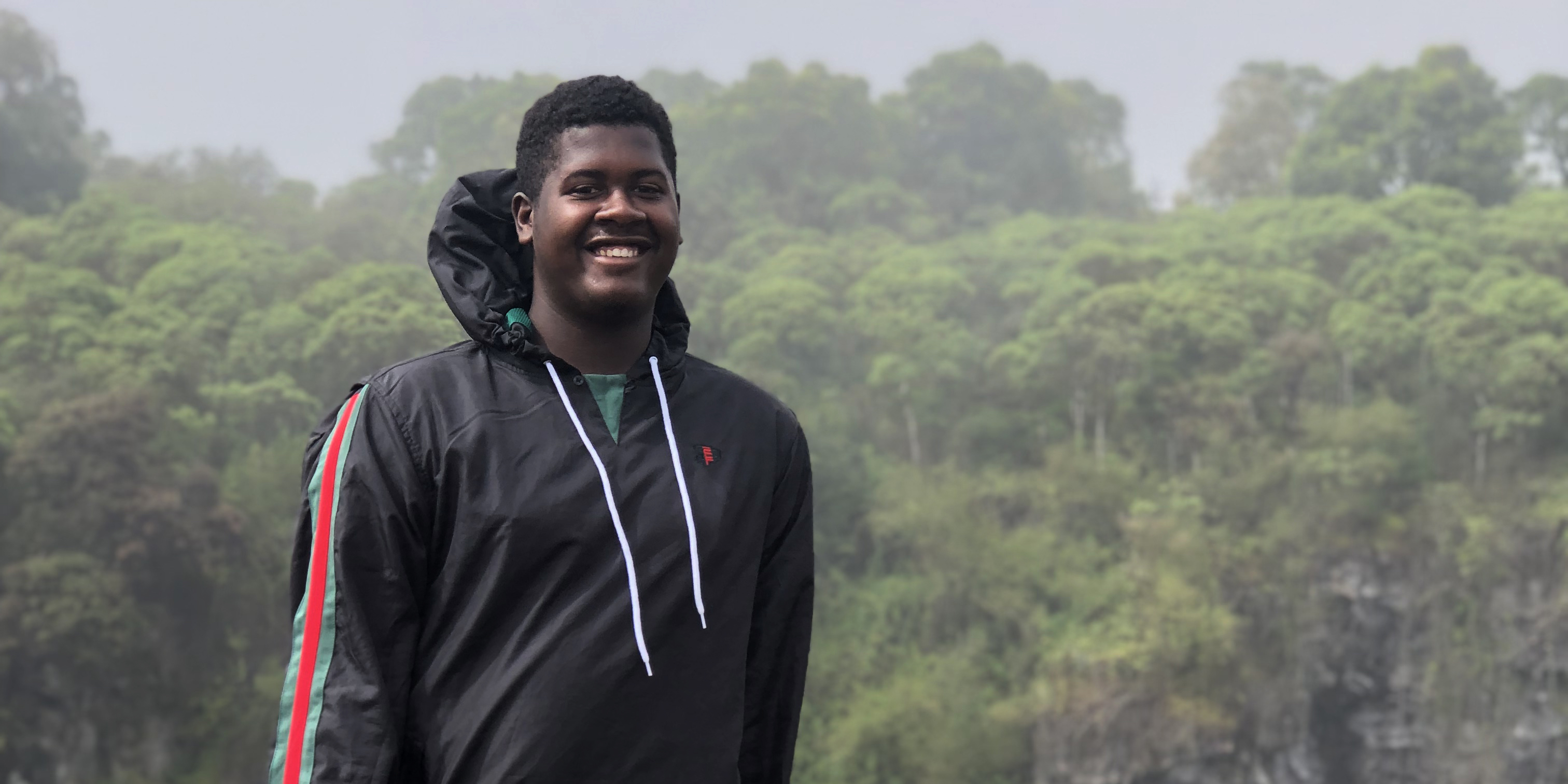 A student smiles with rainforest in the background