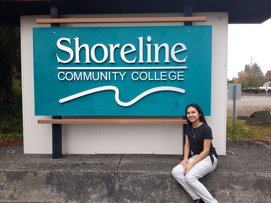 Student in front of a college sign