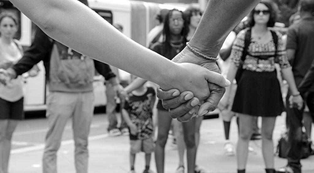 black and white photo of people holding hands at a protest.