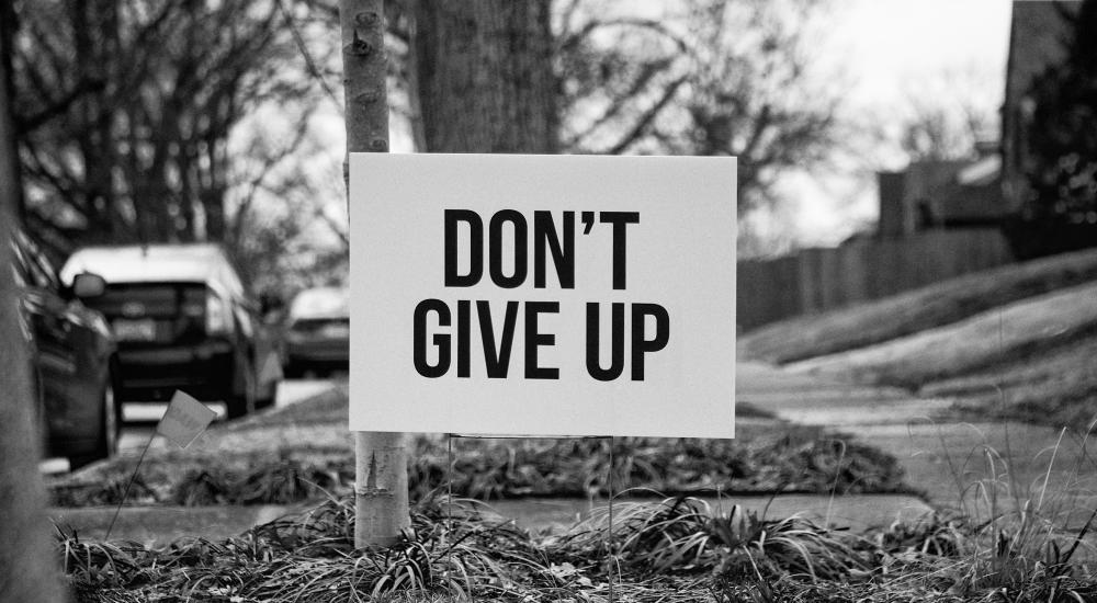 Yard sign that says, Don't Give Up