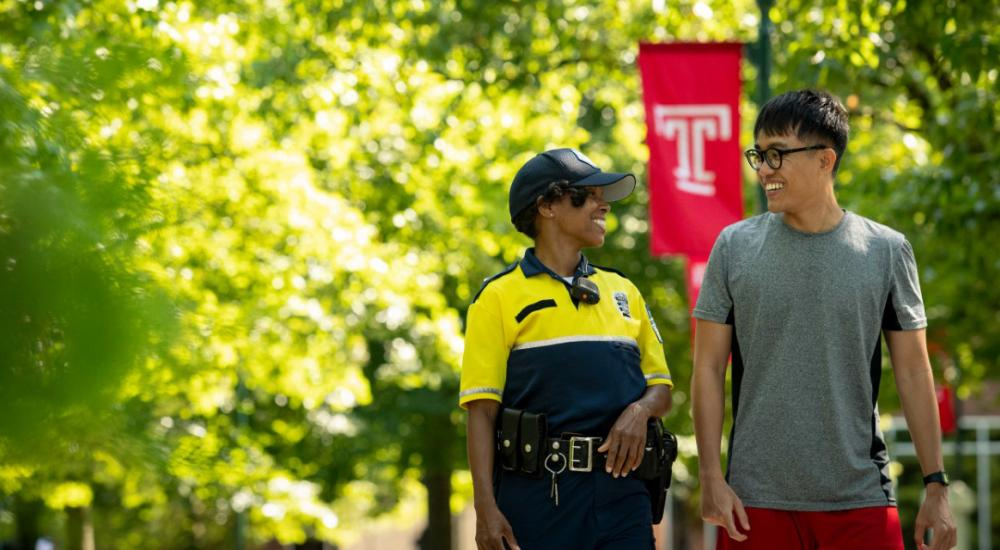 International student and police officer walking on campus