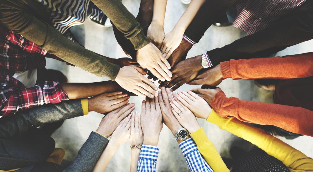 Many peoples' hands in the center of a circle.