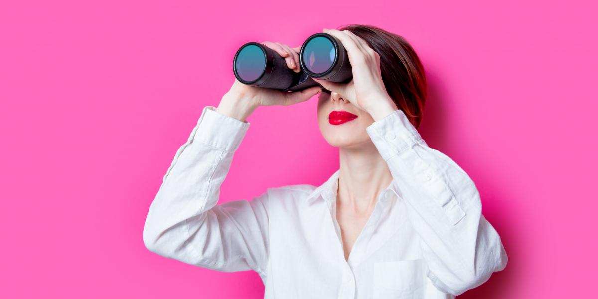 Woman looking through binoculars against a pink background