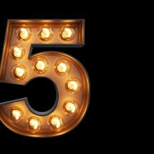 The number five in theater-style lights